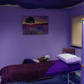 The relaxing treatment area, with dim lighting, soft music and a comfortable massage table